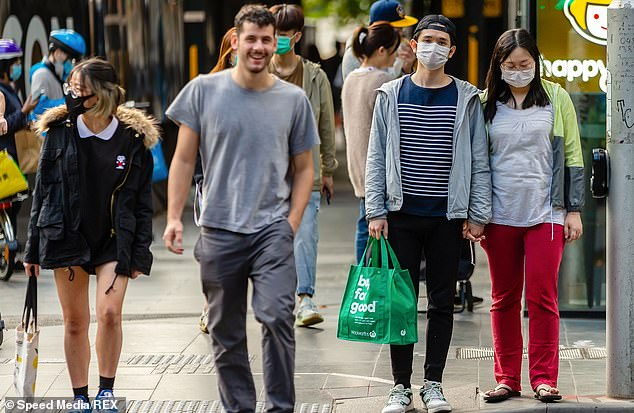 Pedestrians are pictured in Melbourne CBD on Monday with many of them wearing protective face masks