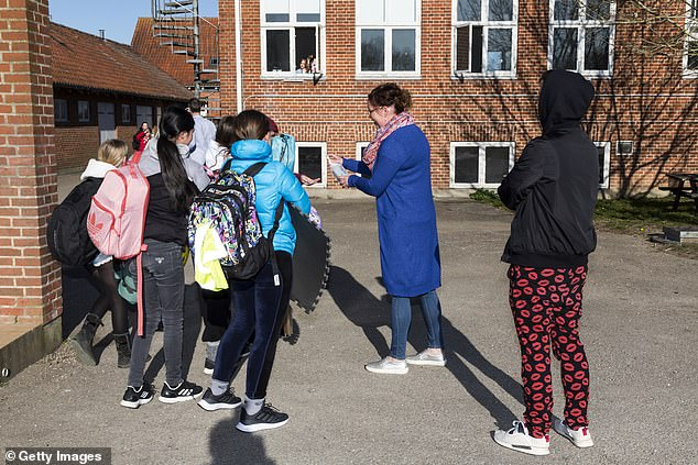 DENMARK: Teacher Louise Sjoestein distributes hand sanitizer to students at a school in Ringsted on Monday