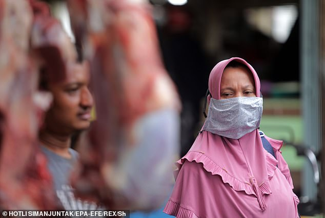 An Indonesian woman (R) wears a handmade protective mask when buying beef on a temporary meat market before Ramadan in Banda Aceh, Indonesia, April 23, 202020