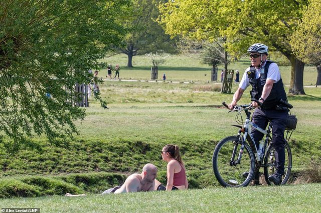 The officer patrolled around grassy areas speaking to couples who seemed to be out for more than just exercise