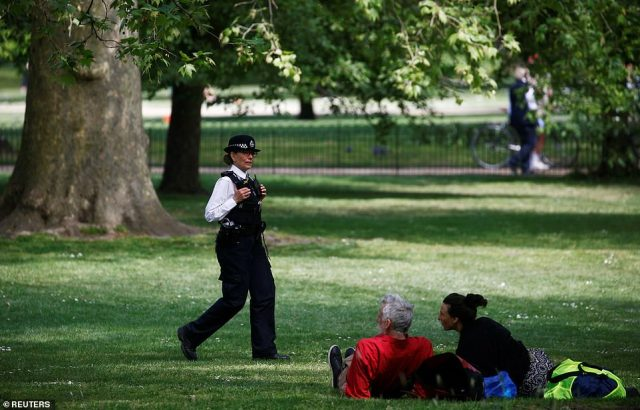 A policewoman was seen talking to a couple sitting on the grass in St James's Park on Sunday