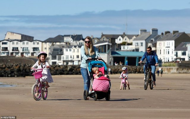 In Portrush, Northern Ireland, a young family brought their bikes out to amble along the wet sand at the beach
