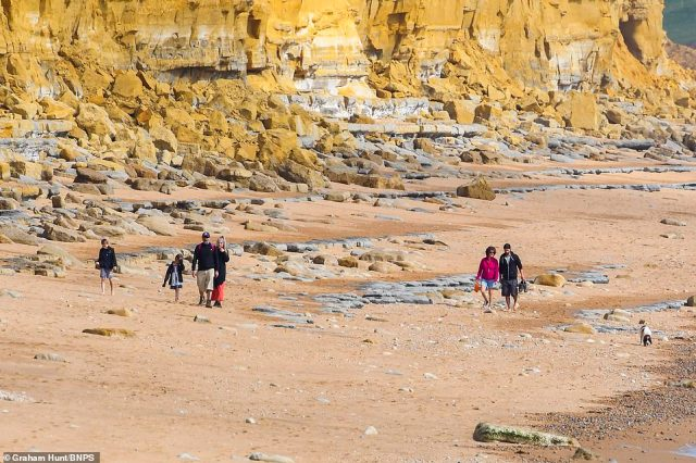 Sun seekers also headed to the seaside resort of West Bay in Dorset to walk beneath rocky cliffs with their dogs