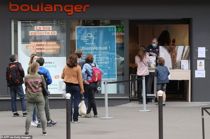 People line up in front of French electronics retailer Boulanger to retrieve orders after stores have been authorized to operate `` click and collect '' services despite the lockout