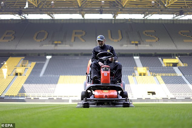 A field officer prepares a field at Borussia Dortmund stadium on Sunday afternoon