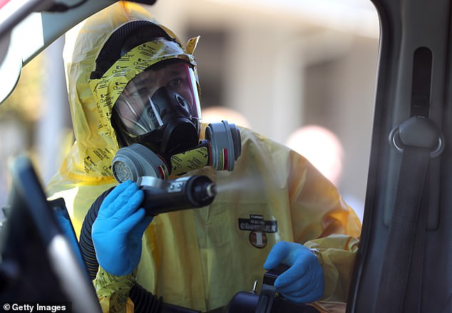 A worker with a disinfectant is pictured spraying an ambulance in California earlier this month. According to several psychologists, the horrors of COVID-19 and the frightening ways in which it disrupted everyday life infect dreams and reveal feelings of fear, isolation and sorrow.