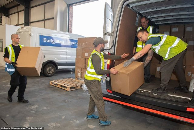 5. Then it's into the vans: Boxes are loaded into one of three Mail Force vans yesterday as the PPE left the warehouse