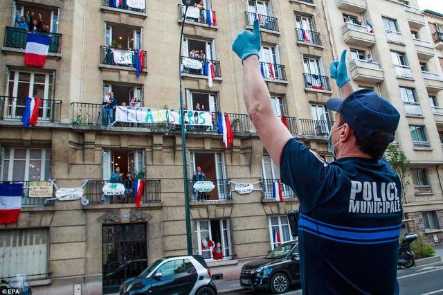 Hospitalisations for Covid-19 and people in intensive care units continued to decline in the country, the French health ministry said. Saturday's daily tally was markedly lower than the 218 recorded on Friday. Pictured: Apolice officer applauds in front of a building decorated with French flags in Saint Mande, near Paris