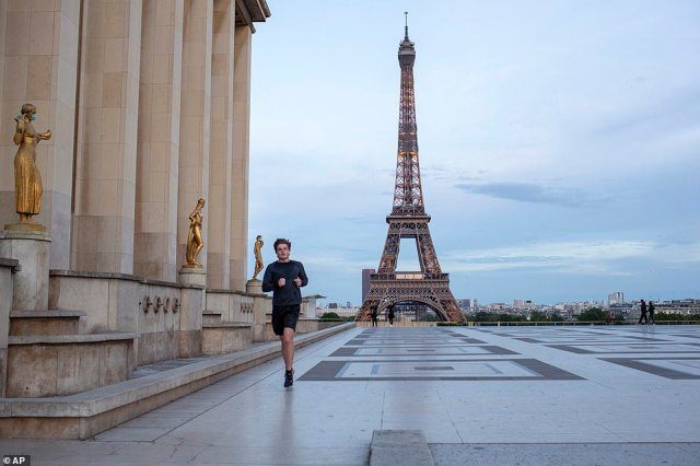 President Macron's government has faced criticism for flip-flopping messages on whether, when and where citizens should wear masks, for failing to replenish the stock of masks before the crisis and for carrying out far fewer tests than neighbouring Germany. Pictured: A man running past the Eiffel Tower on Saturday