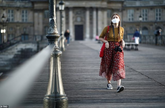 A woman wearing a protective mask walks at the Pont des Arts bridge as the outbreak of the coronavirus disease starts to have less effect in France