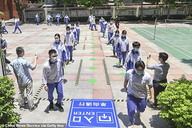 Les élèves portant des masques faciaux font la queue pour faire vérifier leur température avant d'entrer dans une cantine du collège n ° 16 le premier jour de sa réouverture le 27 avril