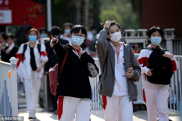 Les autorités de plusieurs grandes villes - dont Tianjin et Shanghai - ont annulé cette année les tests des élèves en raison de préoccupations concernant la condition physique des élèves après la fermeture des écoles. Des élèves portant des masques faciaux sont vus quittant une école à Pékin le 27 avril