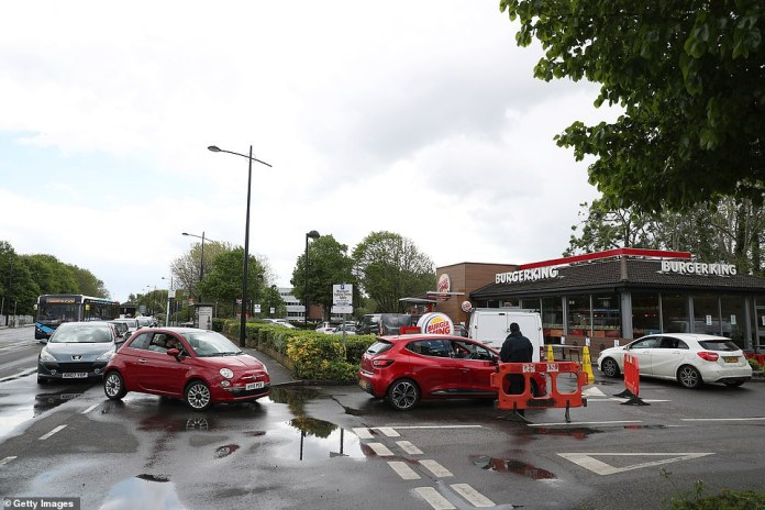 A staff member wearing a face mask and gloves is seen directing cars at the Burger King drive-through in Havant, their first branch to reopen