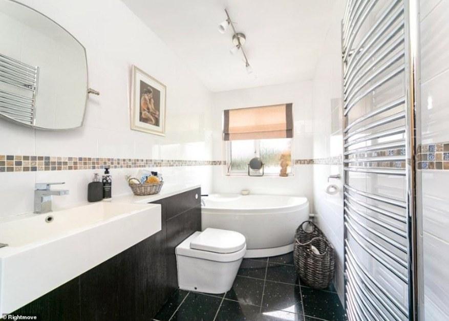 El baño ha sido terminado con un toque moderno con elegantes azulejos y una gran bañera de esquina. La ventana ofrece mucha luz natural.