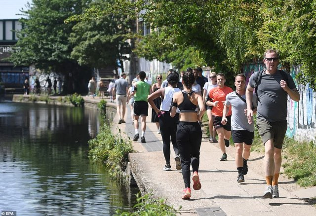 Residents jog and walk along the the Regents canal in London, where hundreds of people were out getting their exercise
