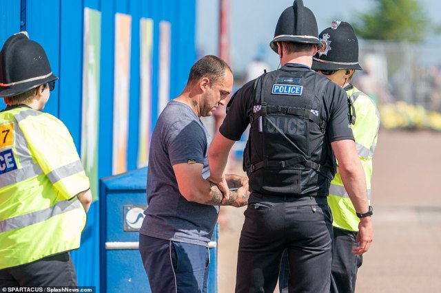 A man is stopped by police officers on the beach in Essex after ignoring the government's guidelines to stay at home