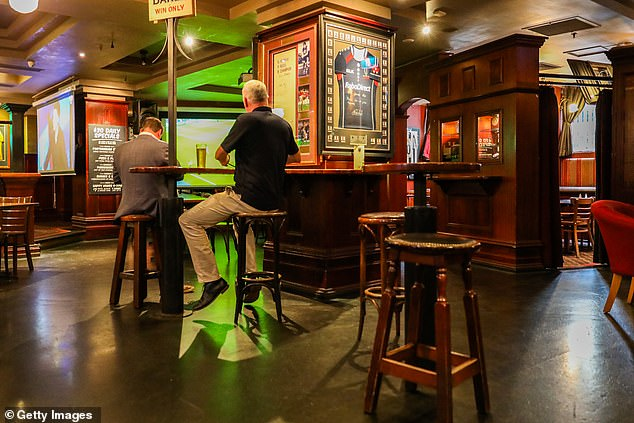 Under stage one of eased restrictions, dining areas can have ten customers inside. Pictured: two patrons in an empty hotel in Melbourne CBD in March