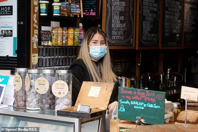 Cafe and pub owners say it will be impassable to make a profit while operating under the governments coronavirus restrictions. Pictured: a barista atWorkshop Expresso Cafe wearing a protective face mask on May 5