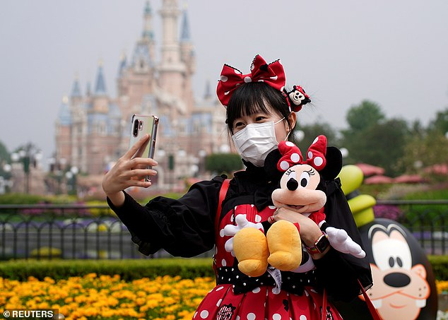Shanghai Disneyland has become the first Disney resort to reopen after it closed to stop the spread of the coronavirus. In the photo, a visitor disguised as a Disney character takes a selfie on Monday