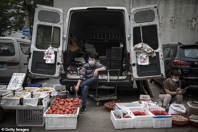 The number of new cases reported in China since April is low compared to the thousands confirmed every day in February, thanks to a national screening, screening and quarantine regime. A seller is seen selling vegetables on a street in Wuhan on April 23