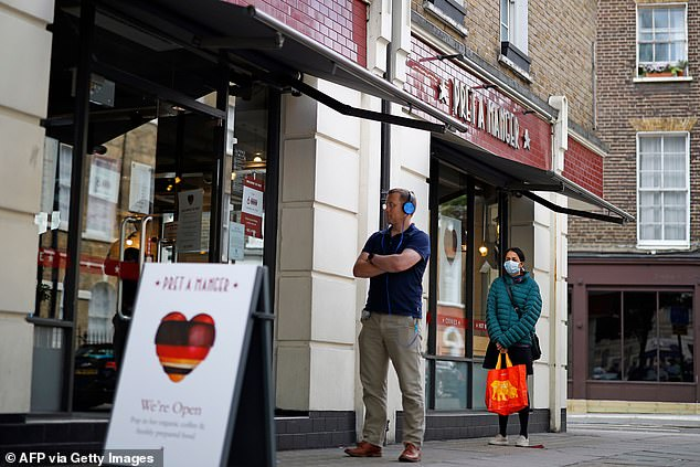 Customers embrace social distance when queuing to enter a recently reopened Pret-A-Manger store in London. The sandwich chain has announced the opening of 71 new outlets from Monday, May 11