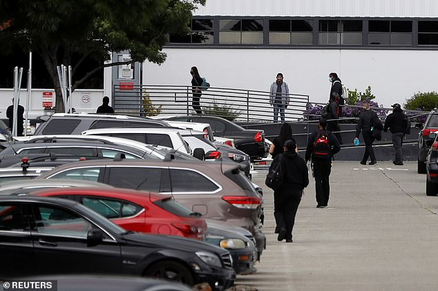 Employees are seen entering the Fremont facility on Monday. Sources said that Tesla threatened to fire them if they refused to return to work amid the lockdown
