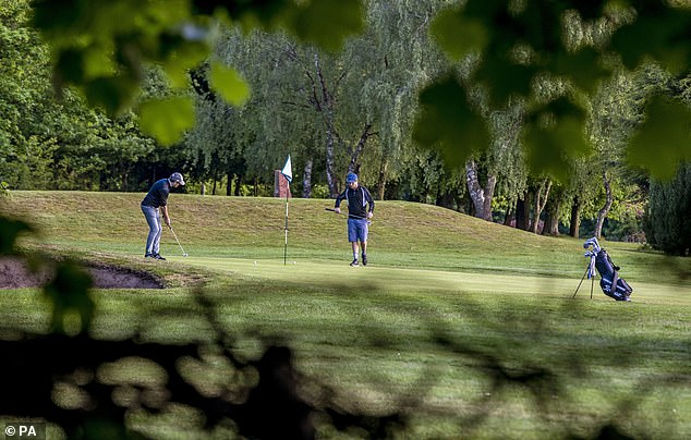 Golfers putt on the 9th green at the Allerton Manor golf course in Liverpool after the lifting of lock restrictions on certain leisure activities today