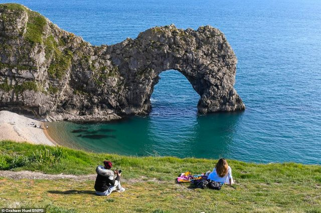 The forecast comes as the government plans to relax lockdown restrictions. Pictured - sunbathers sit at the picturesqueDurdle Door at Lulworth in Dorset, which is now re-opening following initial coronavirus closures
