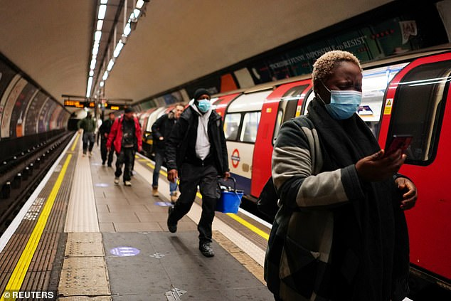 Boris Johnson announced on Sunday that lockdown was easing and people should return to work if they could in a plan to reboot UK's economy. Pictured, a woman wears a protective face mask walks on a platform atClapham Common underground station in London on Thursday