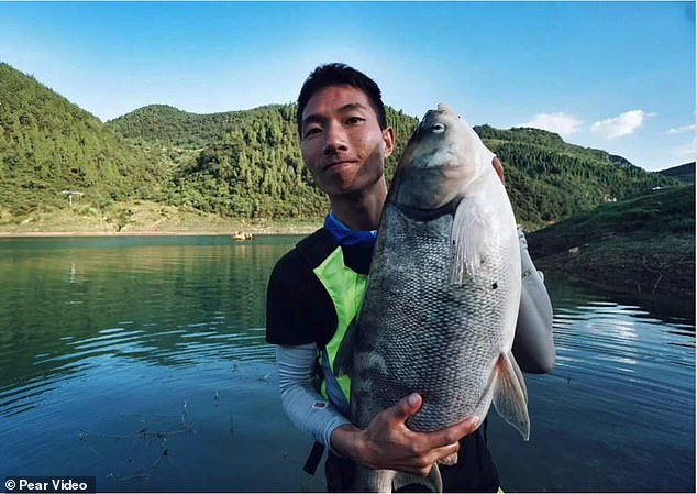 The tourist (pictured), known by his surname Zhou, lost his smartphone when he was catching some fish with his friend on a turbulent river in China last September