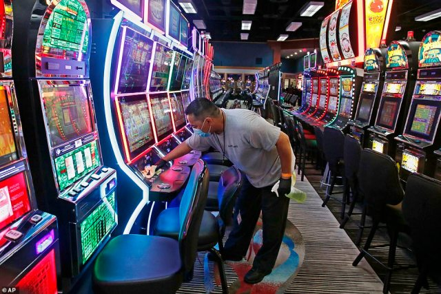 After a customer is done playing at a slot machine at Lucky Star, an employee will receive an alert to clean the machine. Pictured: Tobias Morales disinfects gaming machines in preparation for the reopening of Lucky Star Casino, May 15