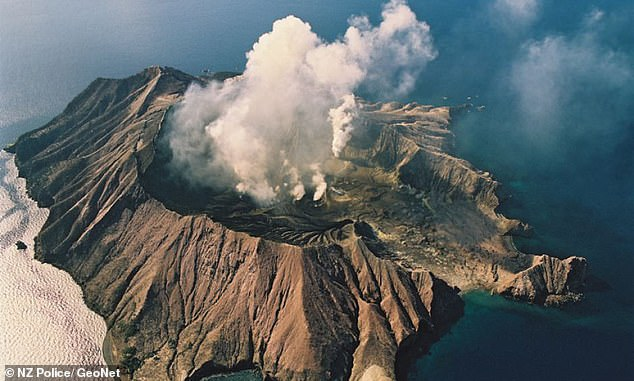 The White Island volcano eruption is pictured from above as a cloud of ash shoots into the sky