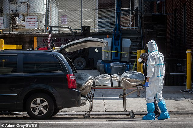 A body is taken away in a vehicle from refrigerated morgue trailers at The Brooklyn Hospital Center, Brooklyn