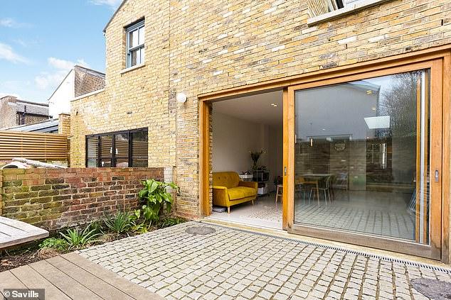 Uma grande porta de correr na cozinha leva a um jardim pavimentado e pavimentado