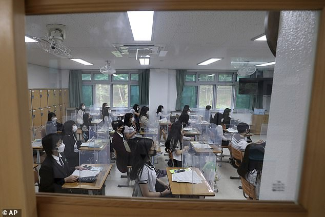 Senior students wait for a class to begin with plastic shields placed on their desks at Jeonmin High School in Daejeon, South Korea, Wednesday, May 20