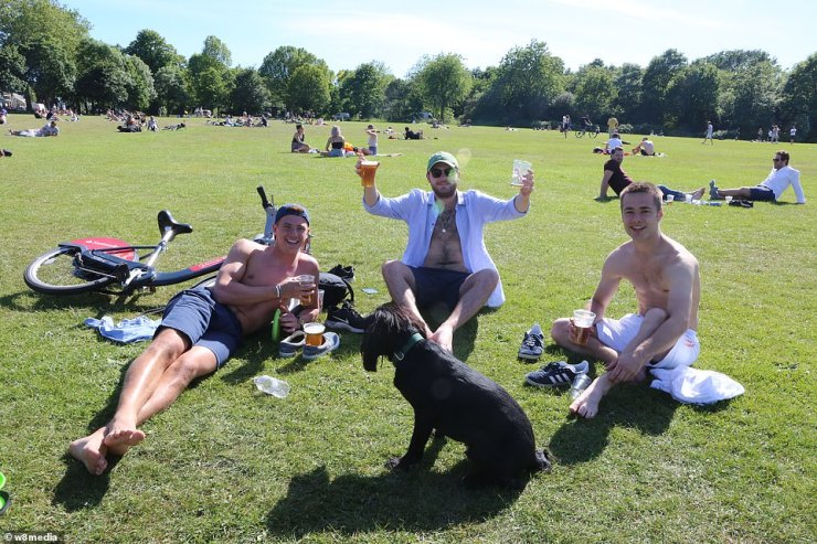 A group of friends sit in Wandsworth Common and enjoy their drinks despite the social distancing measures still in place