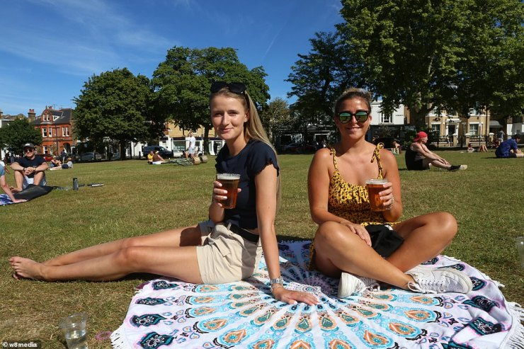 Two sunbathers sat on the grass in Wandsworth Common today as hundreds of people decided to leave their homes to bask in the sunshine