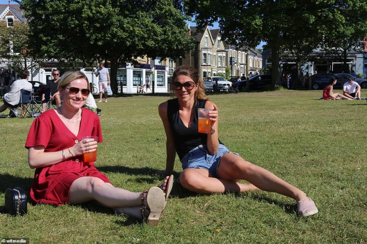 Two people sit on the grass close to The Althorp pub in Wandsworth Common and enjoy beverages on a sunny day