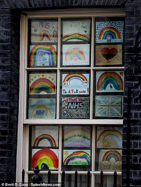 Children's pictures of rainbows adorn the windows at 10 Downing Street