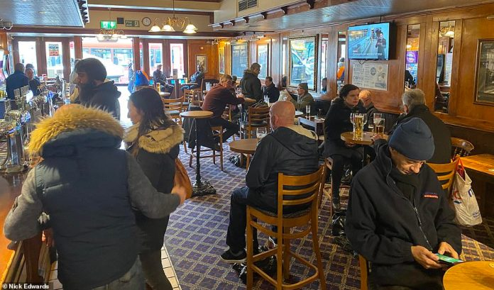 Drinkers are pictured at JJ Moon's Tooting, South London, March 20, the last day of Wetherspoon's national opening