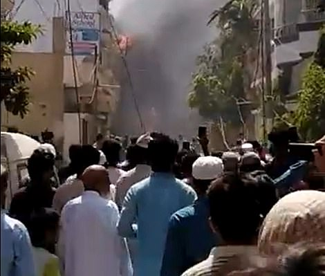 Plumes of smoke billow after the Pakistan International Airlines plane smashed into the residential area