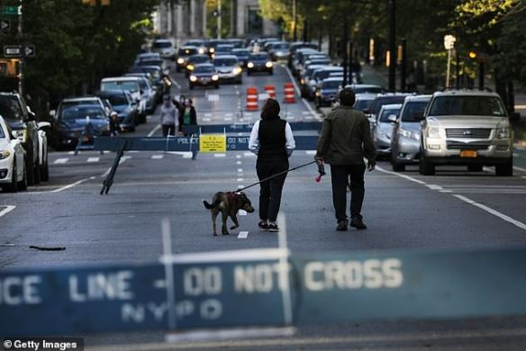 People walk along a street closed to vehicle traffic as the city expands areas for pedestrians to walk and to keep a recommended safe distance in New York City