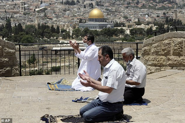 Muslim men pray on east Jerusalem's Mount of Olives, overlooking the Dome of the Rock and al-Aqsa mosque compound, which remains shut to prevent the spread of coronavirus during the holy month of Ramadan on Mat 22, 2020