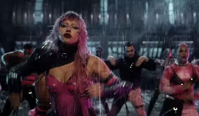 Futuristic: Gaga is seen in a pink latex body as she stops certain movements in the rain