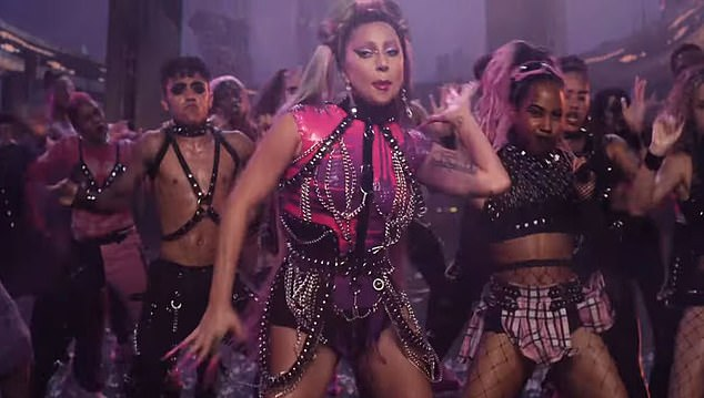 Eye-catching: Another change of outfit shows Gaga in pinker latex as well as studded straps while his dancers wear bondage-style outfits
