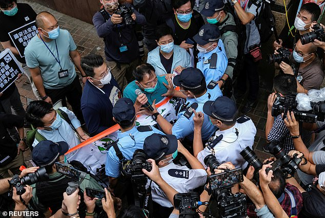 Pro-democracy lawmaker Wu Chi-wai scuffles with police during a march against new security laws near China's Liaison Office in Hong Kong
