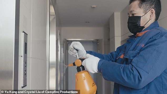 The building's cleaner sprays bleach at lift buttons to prevent the spread of COVID-19. The husband and wife cleaners, Wenling Cao and Quanli Chen, are migrant workers in Shanghai