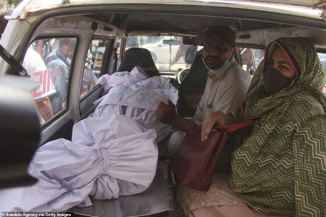Relatives of a plane crash victim recover the body a day after a passenger plane of state run Pakistan International Airlines crashed on a residential colony in Karachi, Pakistan today