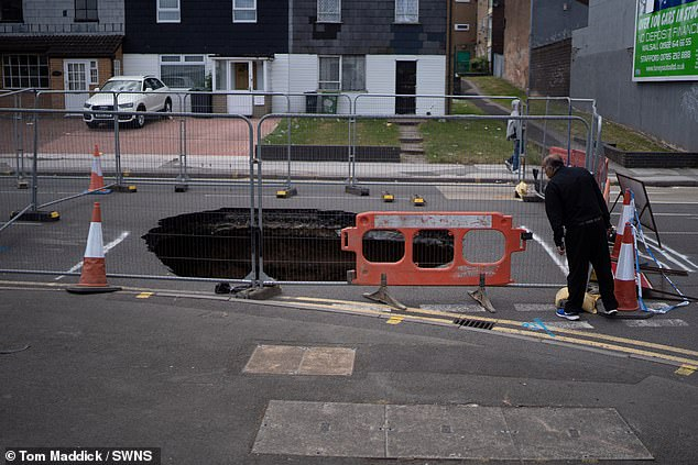 Pictured: A man checks out the depth of the massive sinkhole on a street in Walsall, West Midlands, on Thursday