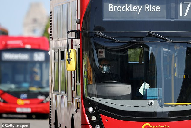 Buses will receive a £254m boost to increase frequency and capacity of services. Pictured: A bus driver wearing a face mask drives over Waterloo Bridge